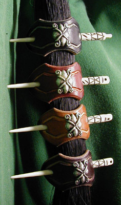 Leather hair barrettes shown in black, chestnut, dark tan and dark brown leathers with hand-carved bone stick and Italian nickel-silver ornament.