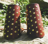 Mercenary Bracers shown in rich, hand-rubbed medium brown leather, heavily studded with brass double cap rivets.